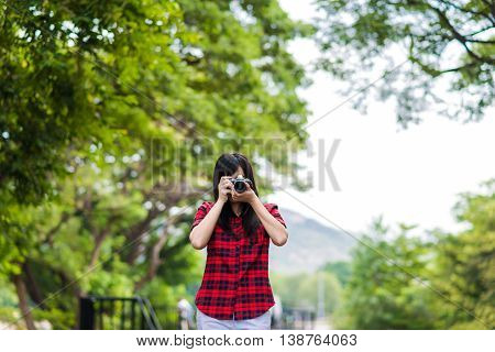 Asian Female Photographer With Mirrorless Camera On Railway