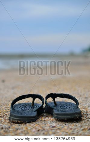 A Summer vacation background with a pair of sandals on beach