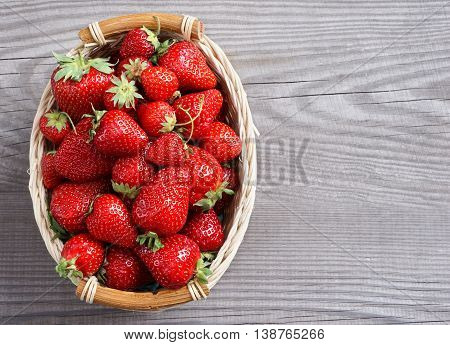 Big strawberry in basket on wooden background. Close up, top view, high resolution product.