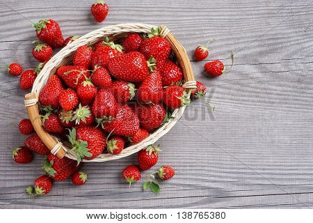 Deluxe strawberry in basket on wooden background. Top view copy space high resolution product.