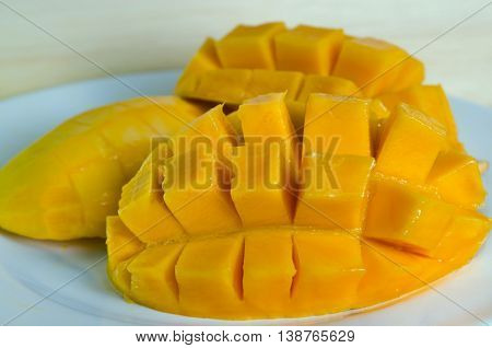 Mango ripe with nicely cut pieceson the plate on wooden board (Other names are horse mango Mangifera foetida Anacardiaceae Mangifera M. indica)