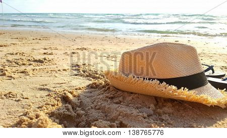 a straw hat and flip flops on the sand at the beach