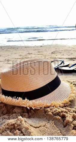 hat and flip- flops on the beach