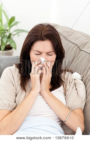 Portrait of a sick woman blowing her nose on the sofa at home