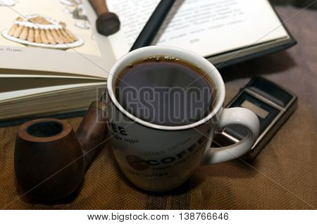 A cup of coffee on  a wooden table with book, pipe and lighter