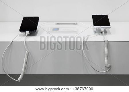 Two smartphones on a white showcase with antitheft system