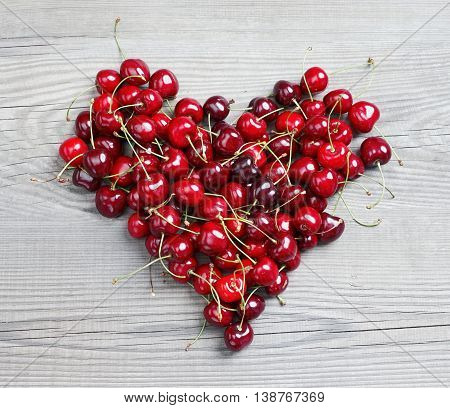 Heart made from cherry on wooden table. Fruits diet concept. Top view high resolution product.
