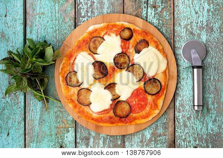 Homemade simple pizza with eggplants tomatoes and mozzarella with basil bunch and pizza round cutter overhead view