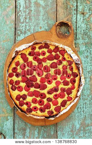 Homemade yummy cake with raspberries baked in foil on wooden board overhead view