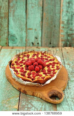 Homemade yummy cake with fresh raspberries on wooden board vertical