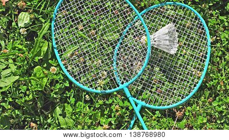 Two green badminton rackets in the grass