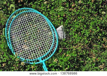 The Badminton rackets and shuttle in the grass
