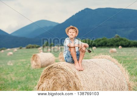 Boy sits on the haystack top .