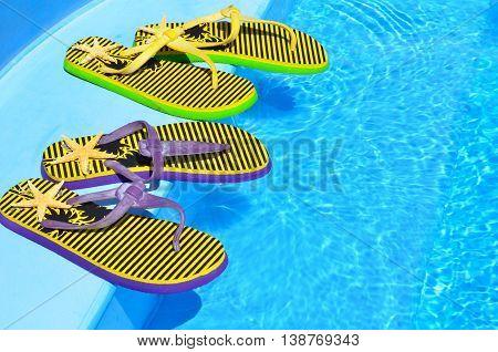 Flip flops on the swimming blue pool.