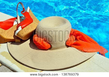 Woman beach hat red sandals on the pool background.