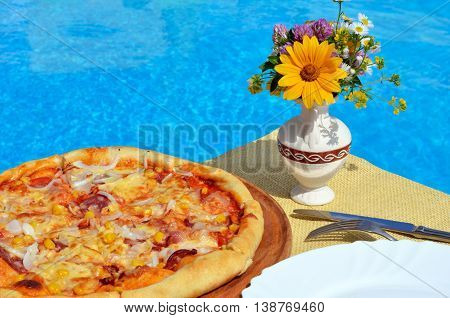 Pizza with corn onions and smoked on a background of the pool.