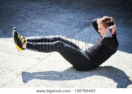 Athletic male in tight clothes makes exercise for the press