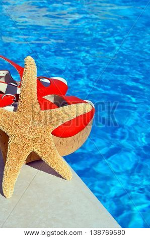 Women's sandals and starfish on the pool background.