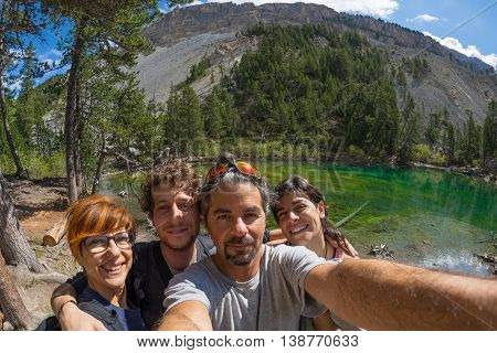 Four young people taking selfie in idyllic landscape with green lake conifer woodland and mountains in background. Scenic fisheye distortion. Concept of traveling people and nature beauty exploration.