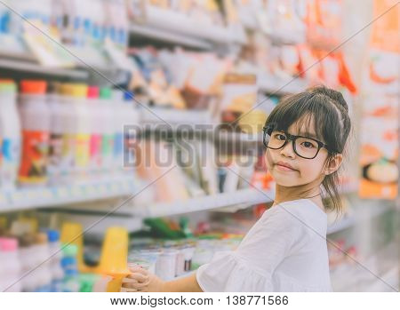 Girl at the shopping mallPortrait of young girl at the shop standing near the shelves with sweets