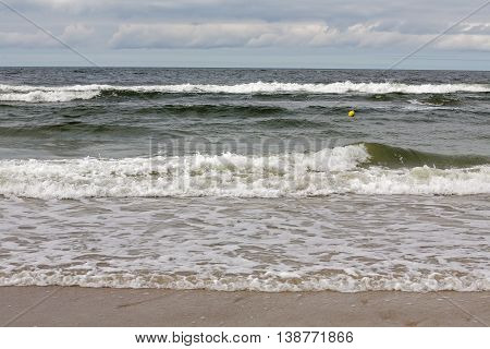 The waves of the Baltic Sea at the shore of a sandy beach in Kolobrzeg in Poland