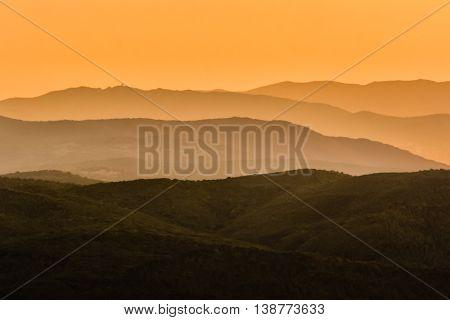 Toscana sunset with hills and orange sky