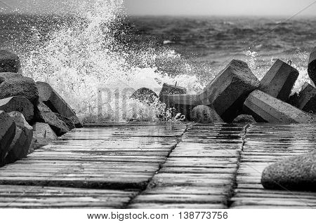 Concrete breakwater in black and white with rough sea