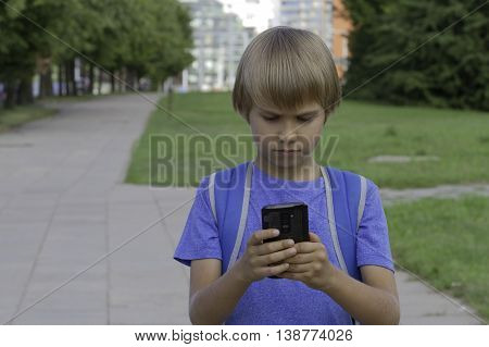 Boy watching apps in the mobile phone. Kid go and use touchscreen smartphone. City background.