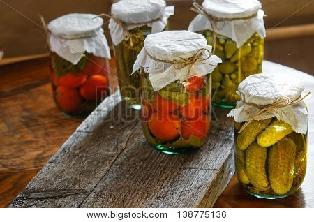 Clear glass jars of colorful pickled vegetables: tomatoes and cucumbers in rustic style