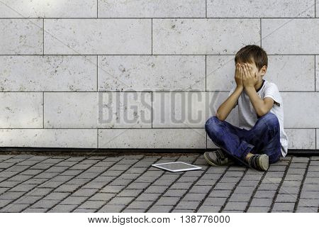 Little boy sad, tired and stressed with tablet computer PC. Kid sitting on the ground, holding his head, close eyes. Outdoor. Education, learning, technology, addiction concept,