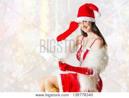 Attractive woman in Santa Clause outfit reading letter to Santa. . Christmas background
