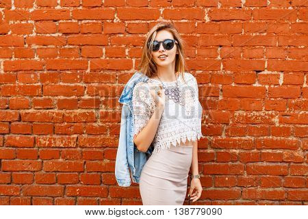 Beautiful Woman In Stylish Vintage White Blouse With Denim Jacket. On The Background Of Red Brick Wa