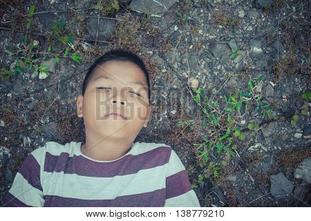 scared and alone, young  Asian child who is at high risk of bing bullied and abused
