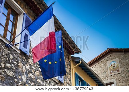 French and European flags hanged on an ancient city hall at french riviera