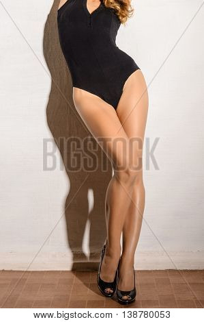 Attractive slender leggy girl in a black body seductively posing in a white wall in the studio