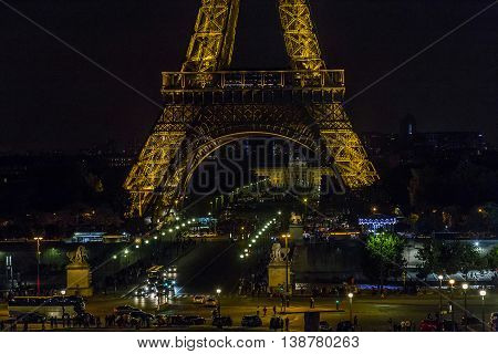 PARIS, FRANCE - MAY 15, 2015: There in night view on Ian Bridge Champ de Mars and the base of the Eiffel Tower.