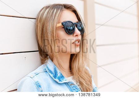 Close-up Portrait Of A Beautiful Young Girl In Sunglasses And Denim Jacket On The Beach Near The Woo