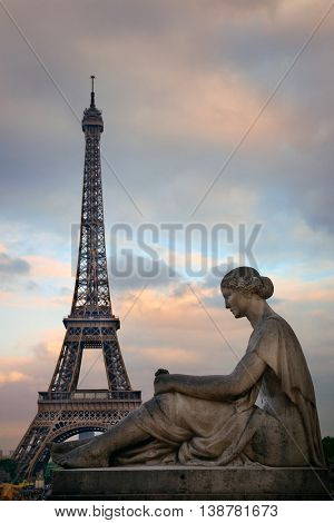 Eiffel Tower with statue as the famous landmark in Paris, France.