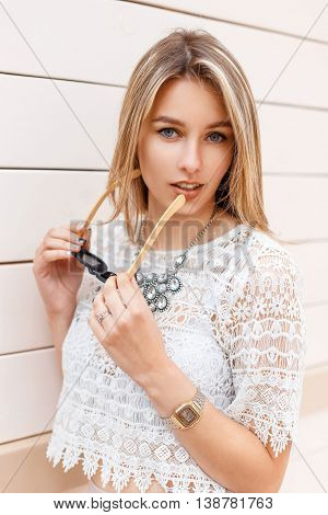 Beautiful Sexy Woman In Vintage Lace Blouse Holding Sunglasses On The Background Of Wooden Wall