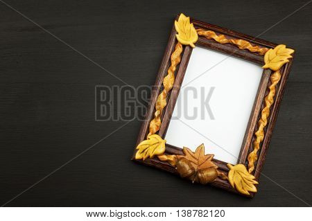 Frame for photos with oak leaves on a wooden background. Wish on a postcard.