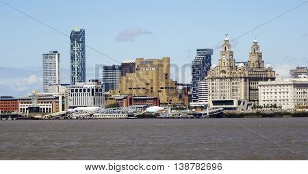 LIVERPOOL, ENGLAND, JULY 3. Pier Head from across the Mersey River on July 3, 2016, in Liverpool, England. Liverpool landmarks include The Royal Liver Building Merseyside Cunard Building Beetham Towers Plaza Unity Residential and New Hall Place.