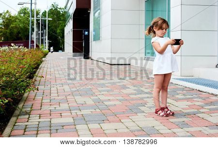 Little girl with a smartphone posing outdoors