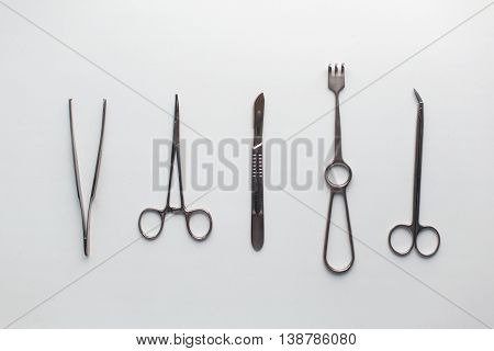 Surgical Instruments (tweezers, Pliers, Clamp The Blade, Scalpel, Scissors) On A White Table.
