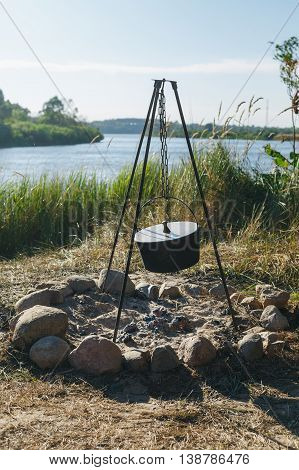 Tourist pot hanging over the fire on a tripod.On the background of the river