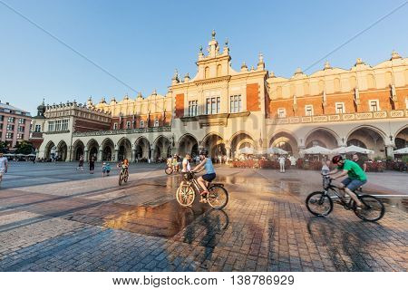 CRACOW, POLAND - June 29, 2016: The Cloth Hall, Polish Sukiennice. People cycling on the main market square. Old medieval town of Cracow is listed as UNESCO heritage site.