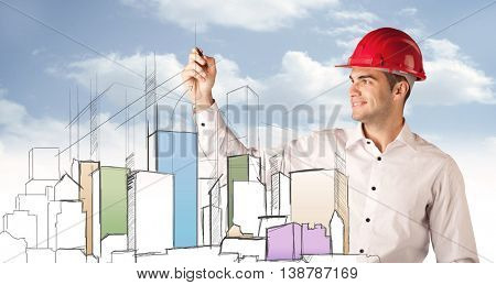 A young construction worker in a red safety helmet happily planning a city sight and drawing lines, arrows, angles, buildings with a pen in his hand