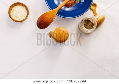 Blue bowl with paprika and oregano wooden spoon black pepper and dehydrated potato on white tablecloth
