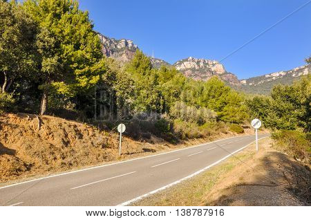 Scenically attractive landscape mountain road with circular speed limit sign with crossed number sixty on it (60 km/h). Horizontal.