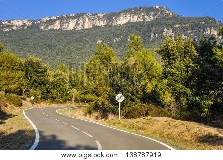 Scenically attractive landscape with mountain road and circular speed limit sign with crossed number sixty on it (60 km/h). Horizontal.