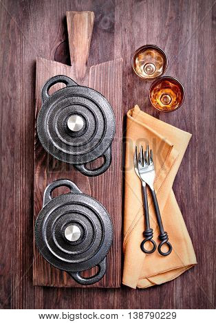 The small cast iron pan with forks and glasses on a cutting board